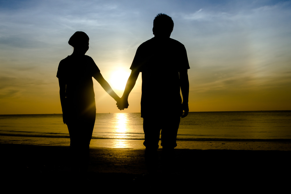 holding hands on sea beach during the beautiful sunset.